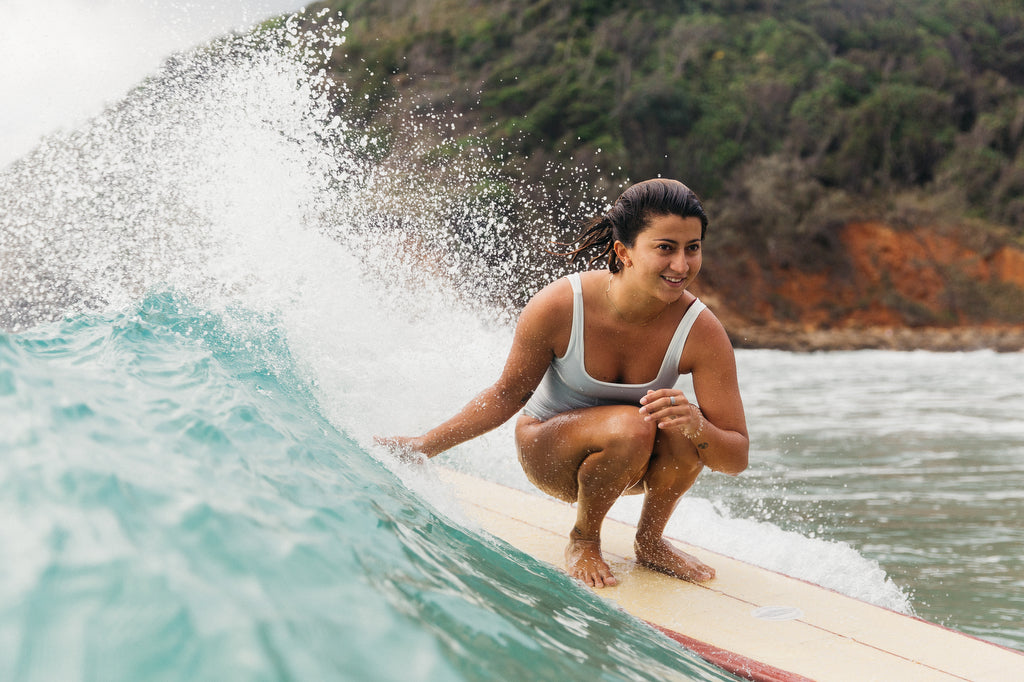 Woman crouched down surfing wearing one piece surf swimsuit in ivory