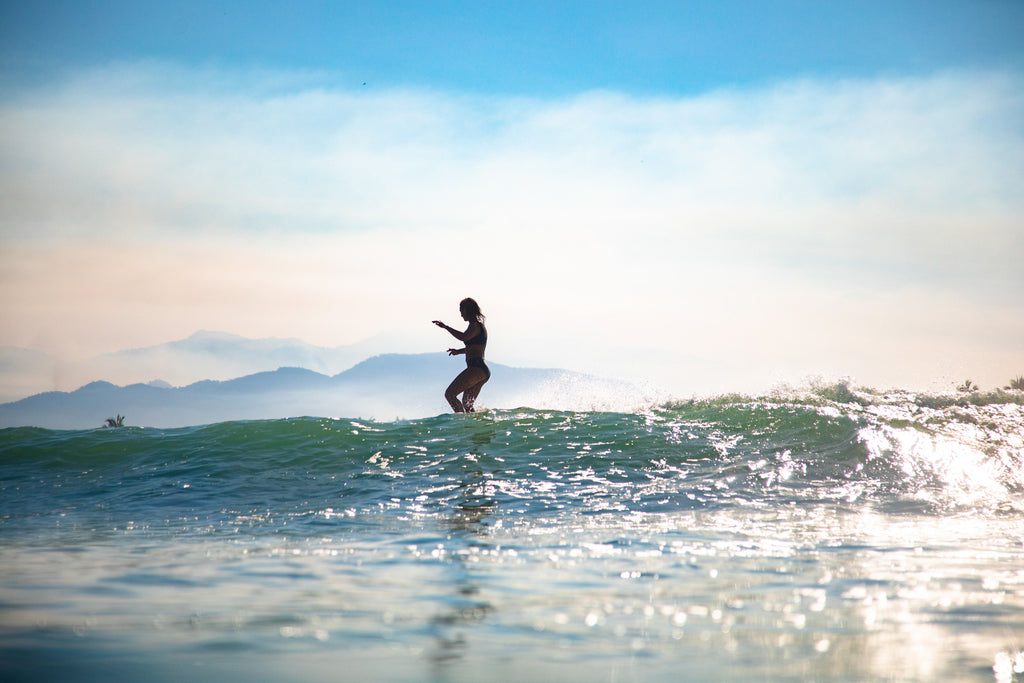 Silhouette of Kassia Meador surfing wearing surf bikini top and bottom in mexico