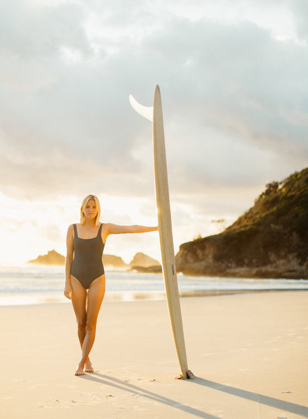 Woman in one piece surf swimsuit standing on the beach at sunrise holding a longboard surfboard