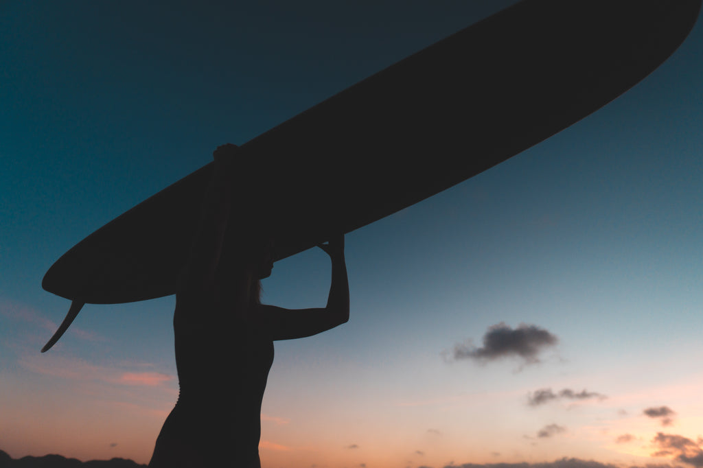 Silhouette portrait of woman balancing a surfboard on her head at sunset