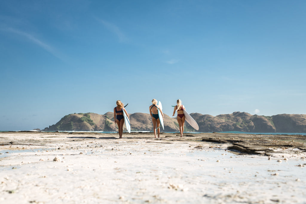 Three women walking away with their surfboards under arm on the beach