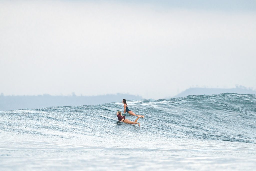 Two women on surfboards paddling over a wave wearing one piece surf swimsuits and rash guard