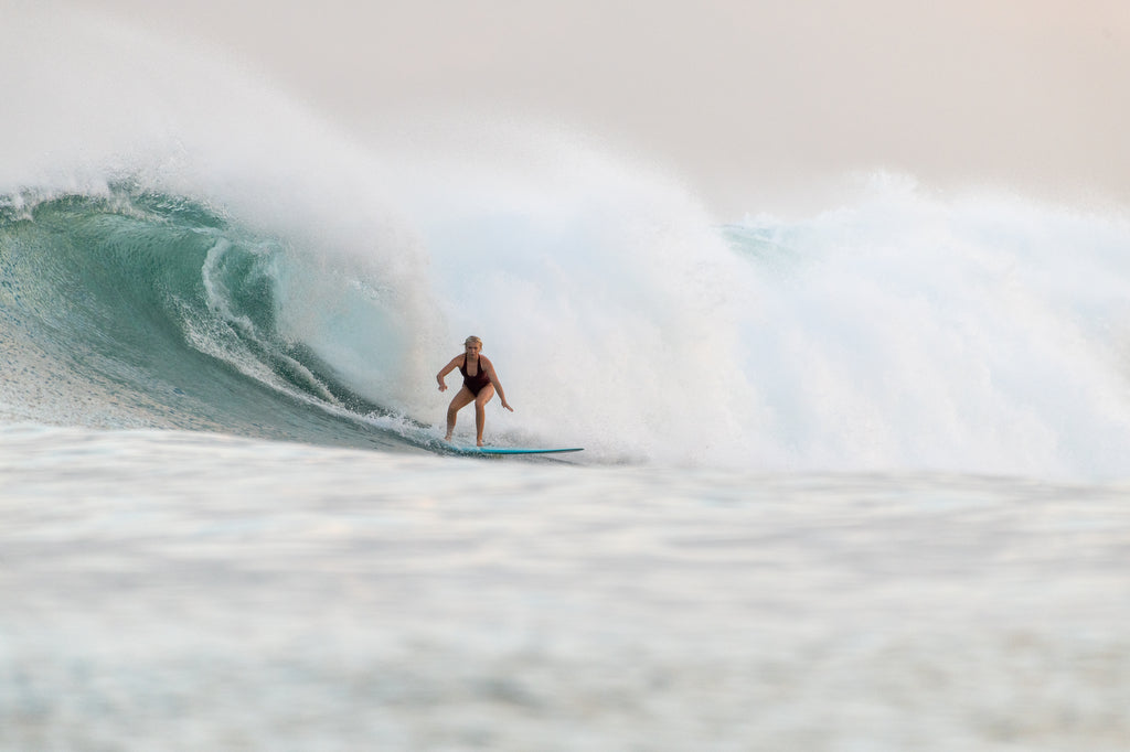 Woman doing a bottom turn on overhead wave wearing Elena one piece surf swimsuit in Indigo