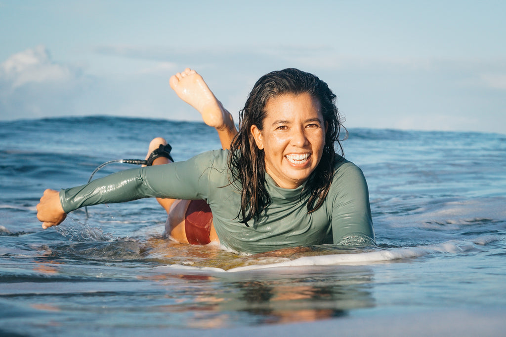 Erika smiling and paddling in the water wearing a rash guard and lucky high waisted surf bikini bottoms