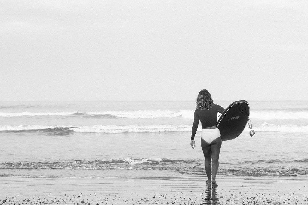 Erika walking to the water with surfboard under her arm wearing rash guard and lucky high waisted bikini surf bottoms
