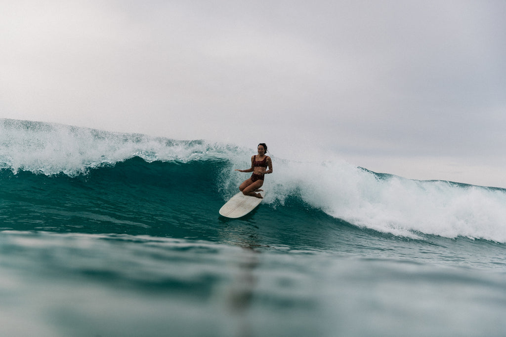 Sierra wiping out on a wave wearing a surf bikini top and bottom