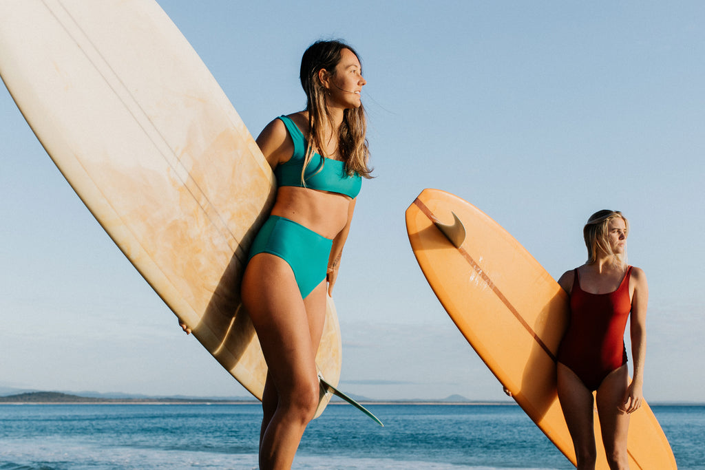 Ivy and Sierra standing on rocks, holding their surfboards, wearing surf bikini top and bottom and one piece swimsuit