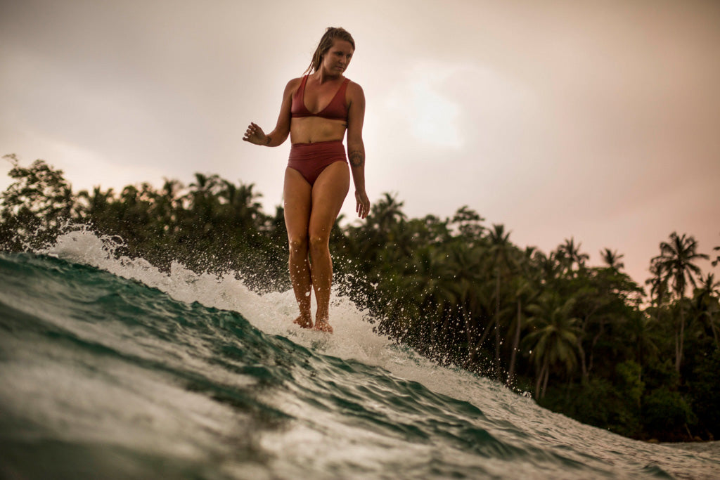Woman noseriding at sunset in surf bikini top and bottom in burnt sienna