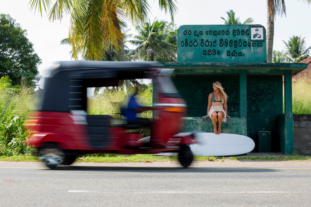 Woman waiting in bus stop with surfboard and tuk tuk on road Sri Lanka