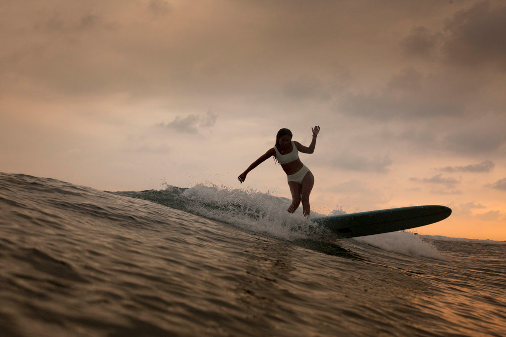 Woman doing a bottom turn at sunset on surfboard wearing surf bikini top and bottom in ivory