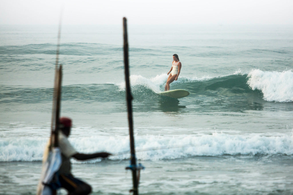 Woman wearing surf one piece swimsuit and bottom turning on surfboard in front on Sri Lanka fisherman