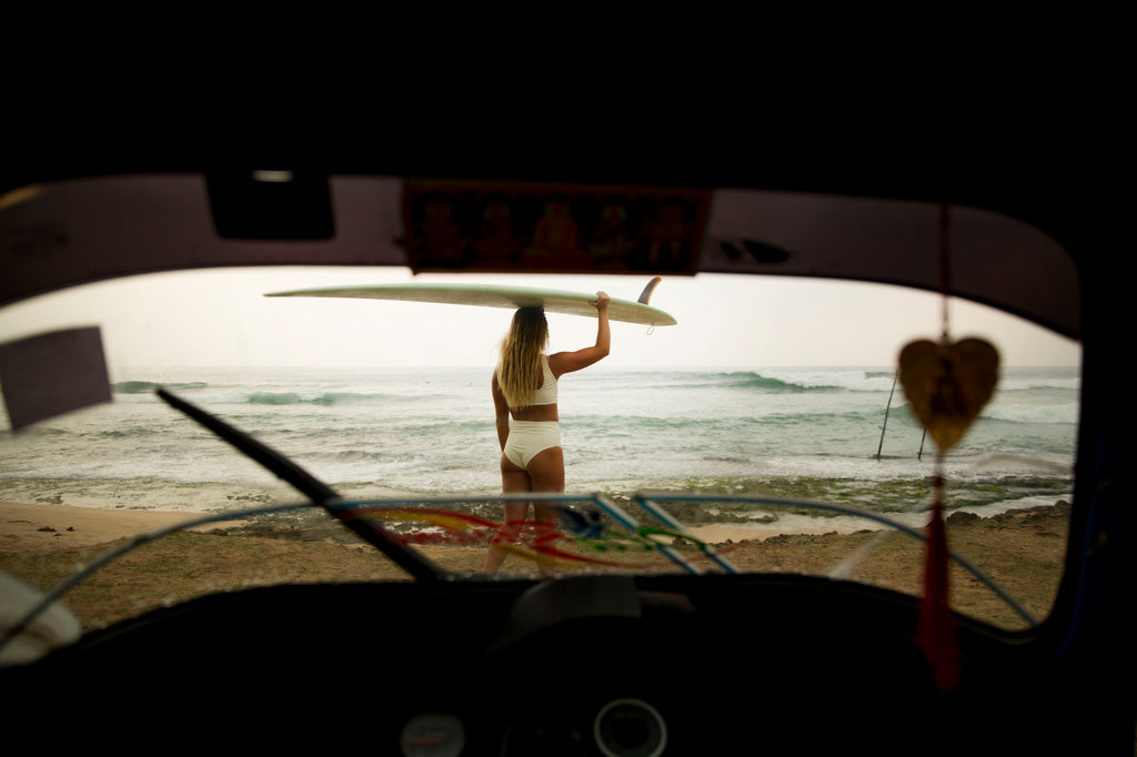 Rainy afternoon view of woman through tuk tuk window walking to the ocean with surfboard on head wearing surf bikini top and bottom in ivory
