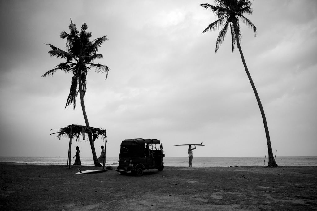Woman looking at the ocean holding surfboard on head wearing a surf bikini in Ivory next to a palm tree and tuk tuk