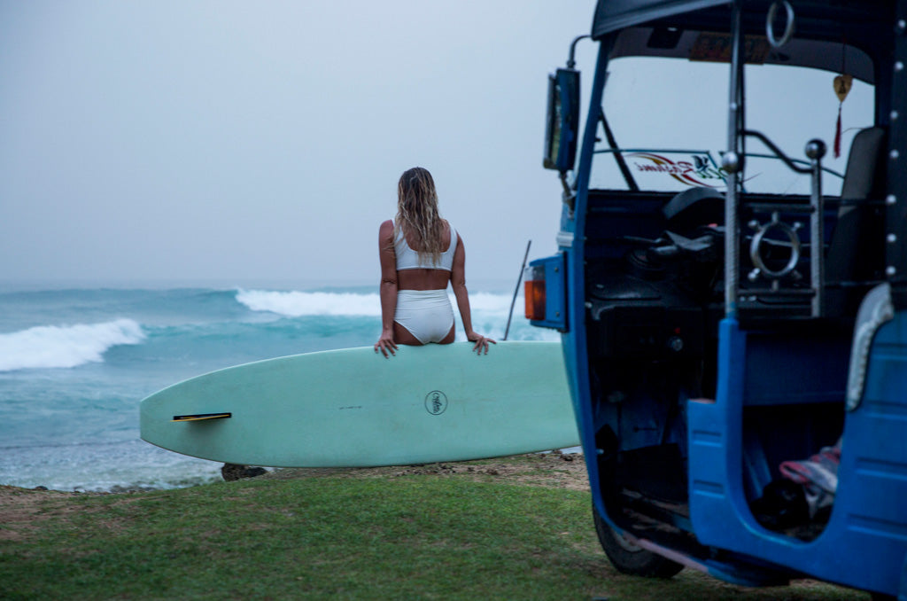 Woman sitting on rail of her longboard wearing surf bikini top and bottom looking at the ocean rainy day