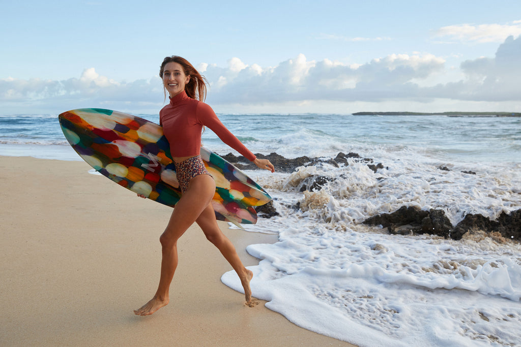 Woman smiling and running from the water with multi color surfboard wearing rash guard and lucky surf bikini bottoms