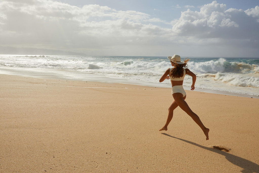 Woman running down the beach in straw hat and wearing surf bikini top and bottom in ivory