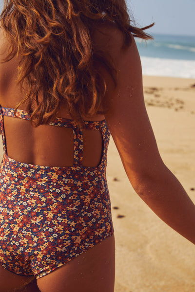 Woman looking at the ocean wearing Paris one piece surf swimsuit in floral print