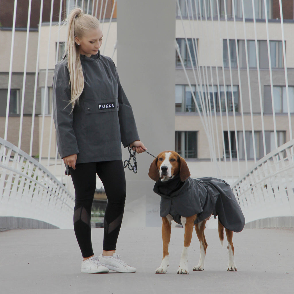 Woman and dog using matching black PAIKKA visibility raincoat