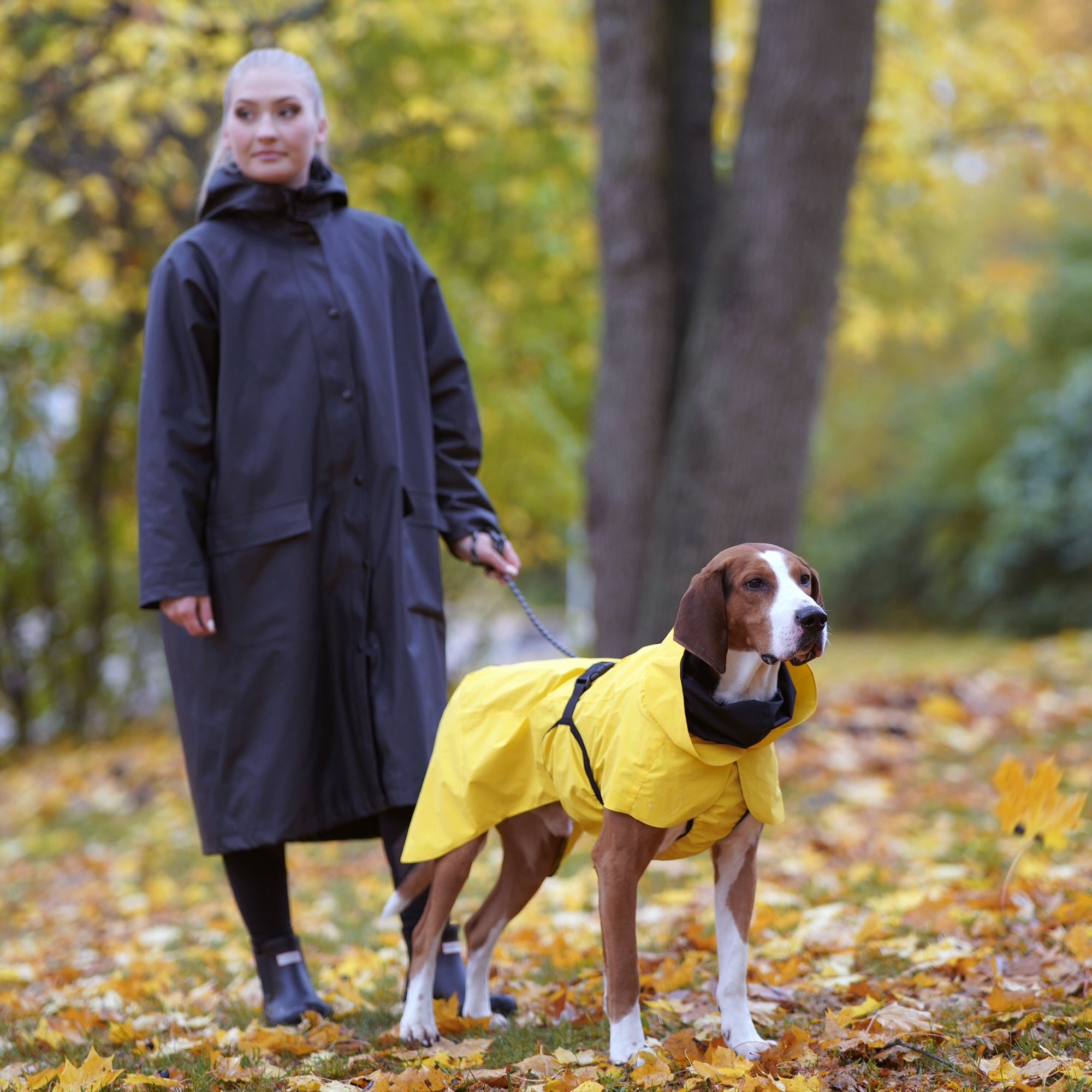 A woman and dog who is using PAIKKA visibility raincoat yellow