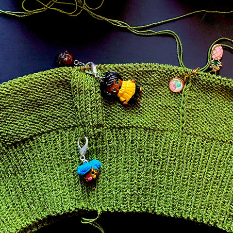 Four stitch markers being used for knit (top) and one progress keeper (bottom)