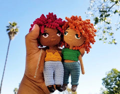 A hand holding two crochet doll with the sky and a palm tree in the background
