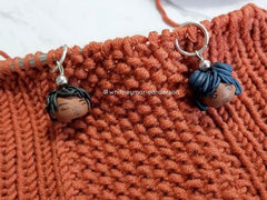 Two Stitch Markers Hanging from a textured knit project in progress