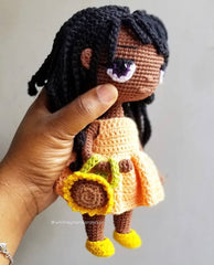 A hand holding a crocheted doll wearing a peach dress and yellow shoes