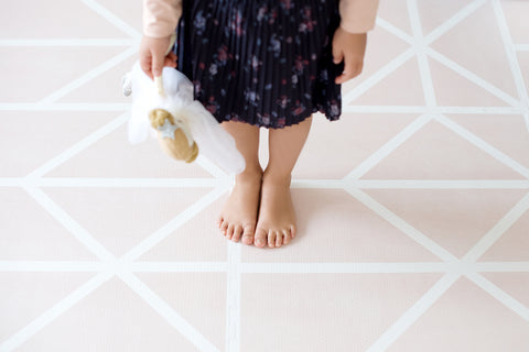 young girl with bare feet standing on a playmat