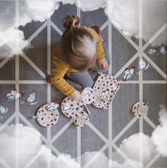 Young girl sitting on a playmat having an imaginary tea party with cloud and butterfly effects