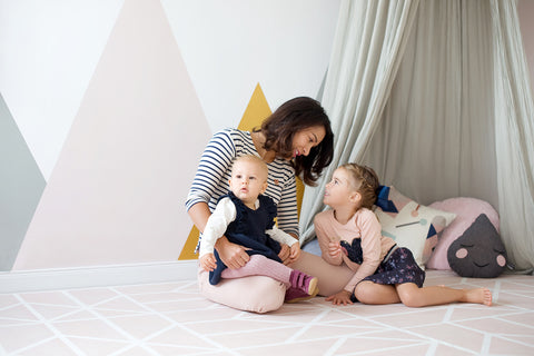 mother and two daughters sitting on a playmat