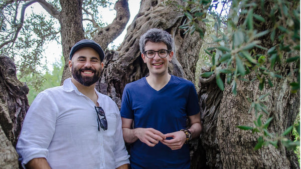 Alex and Hasan, a greek Cypriot and a Turkish Cypriot inside an olive tree holding olives and smiling