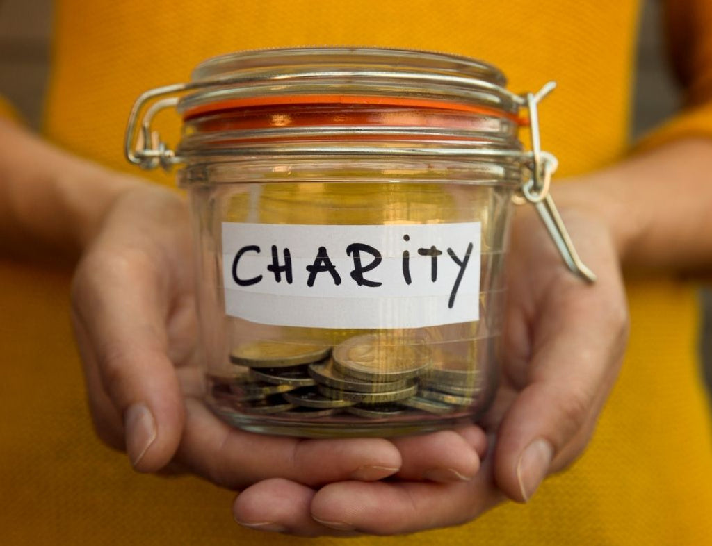 """A jar of change that has the word """"Charity"""" written over it"""