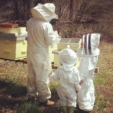 beekeeper and children inspect bee hive