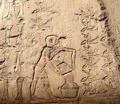 Ancient Egyptian hieroglyphics of beekeeper harvesting honey and dumping into jar