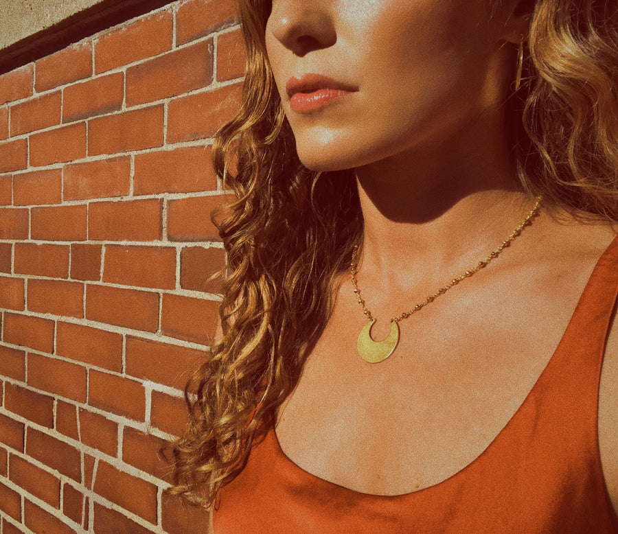 matte gold crescent moon pendant necklace - lifestyle shot - jewelry