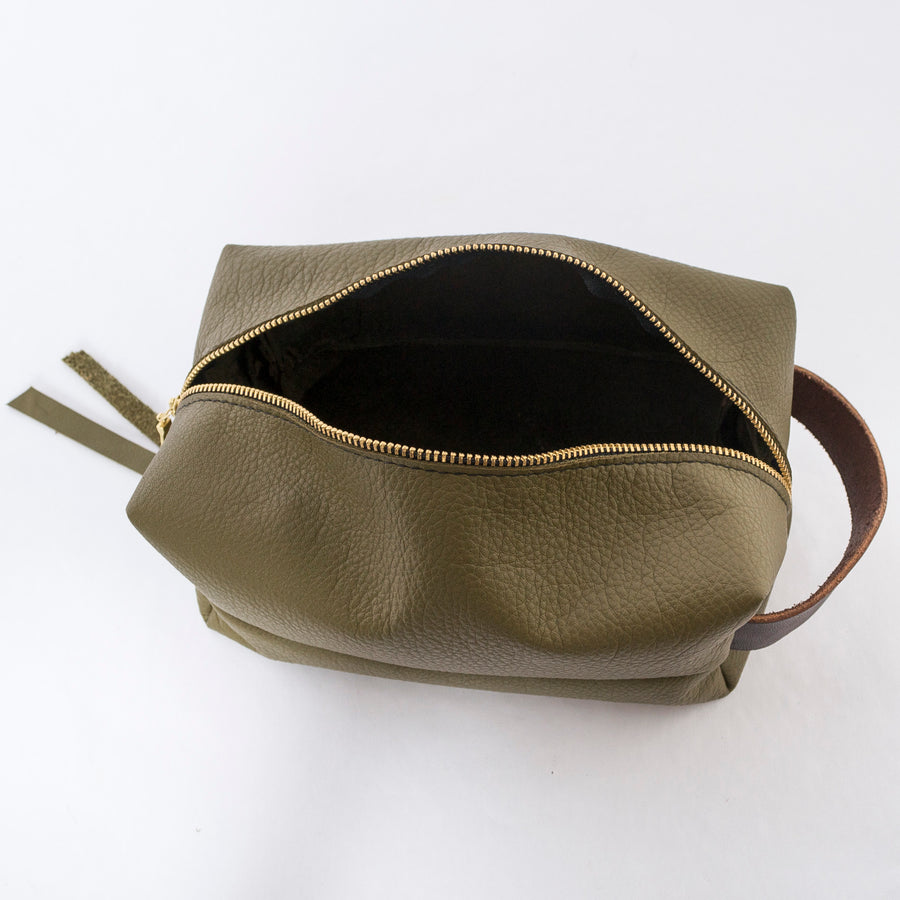 top view of the dopp kit in olive green - open zipper - durable leather bag - handmade in workshop at venn + maker