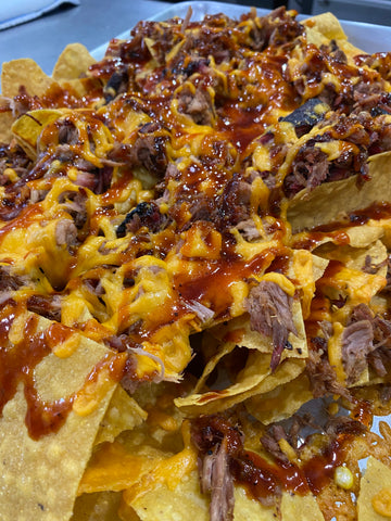 Pulled pork nachos picking up chip