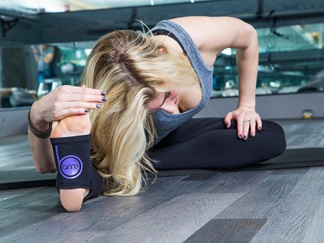 woman holding foot and stretching in barre class