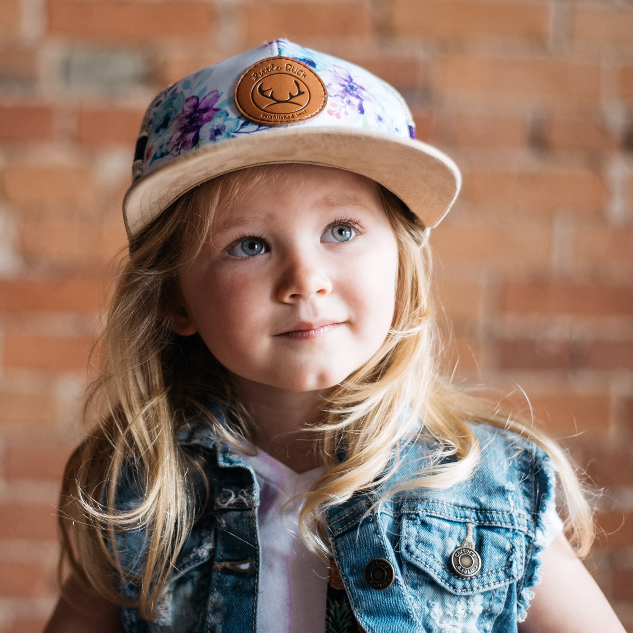 Little girl with blonde hair wearing a jean vest and a floral hat with a leather patch and suede brim