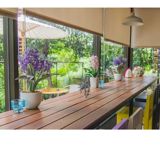 Patio roller shades in a patio with a long wood table and floers on top