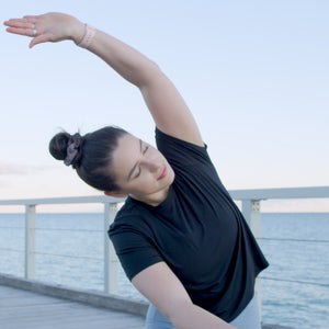 Leah Itsines calm and stretching on a jetty with ocean water behind in Adelaide, South Australia