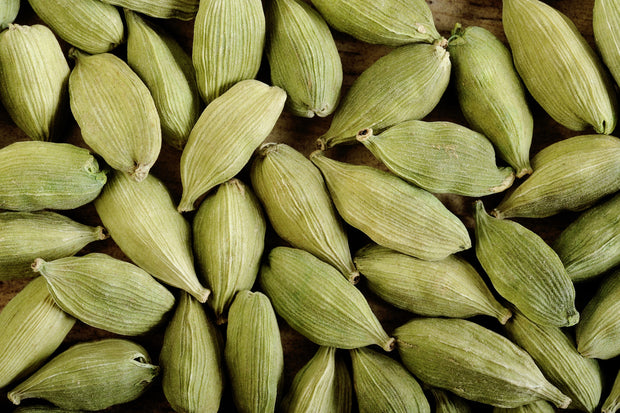 Cardamom Pods On Wooden Background.jpg