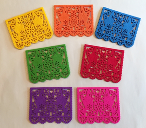 Coasters shaped like individual sheets of papel picado. Each one features a depiction of two doves flying face-to-face with floral accents around the doves. Comes in Pink, Green, Blue, Orange, Yellow, Purple, and Red.