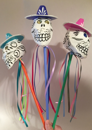 This maraca features a skeleton head with a sombrero. The eyes of each skeleton are made up of rhinestones and 6 colorful ribbons hang down from the base of the head. The head is supported by a long stick which allows the skeleton head to make noise when shaken.