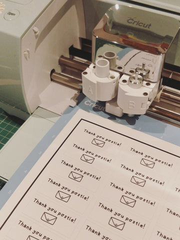 """Thank you postie"" stickers being cut out on Cricut machine"
