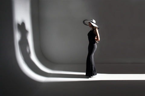 Woman in black dress with silhouette on wall