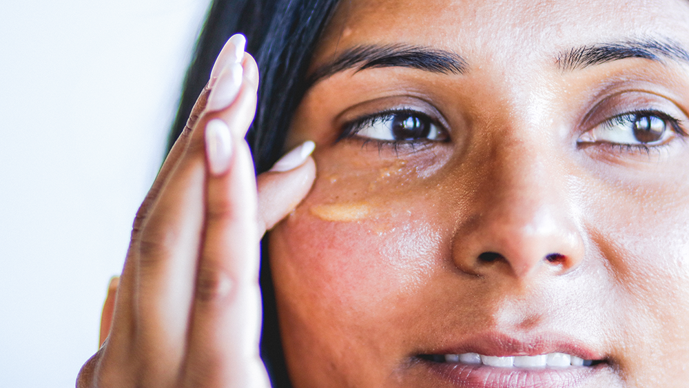 Woman applying niacinamide and vitamin c serum to face
