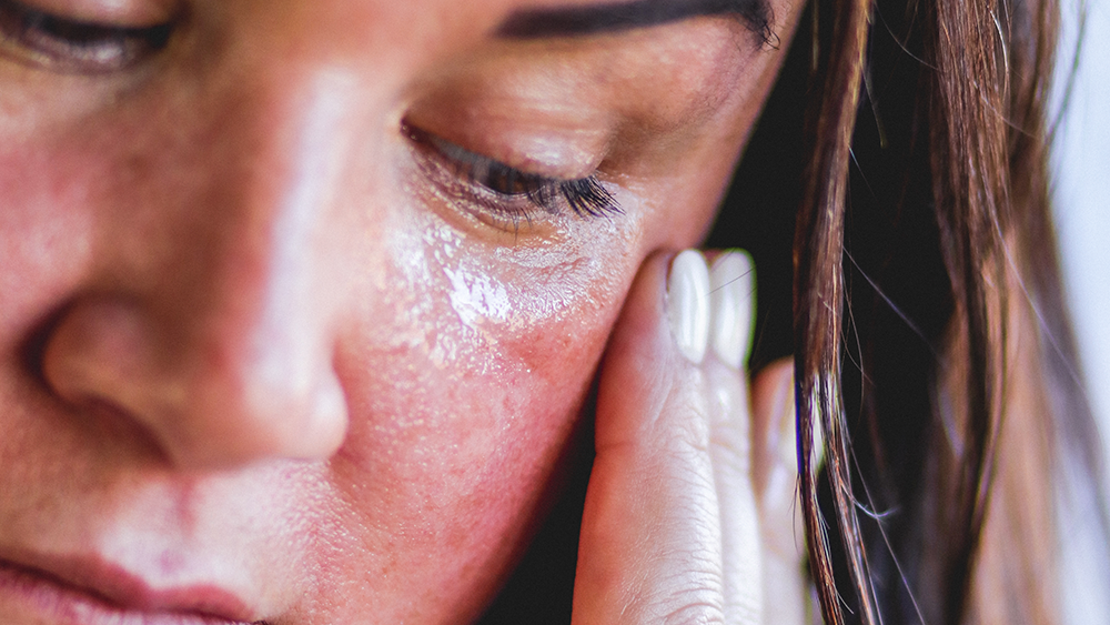 Woman applying niacinamide and hyaluronic acid serum to face