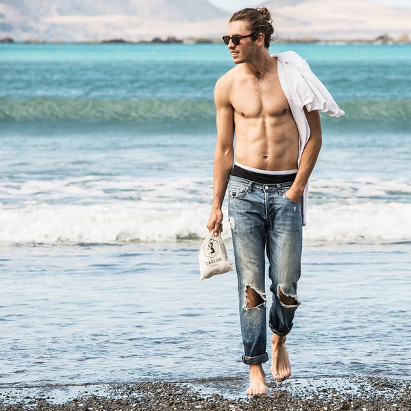 Male Model walks on beach carrying Tailor Tote Bag. Made from Organic Cotton.