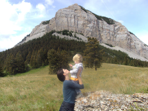 Beth Russell (brown haired woman) holding a toddler, in front of a mountain